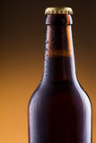 Beer bottle with water drops on golden background. Stock Photo