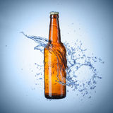 Beer bottle with water splash Royalty Free Stock Photos