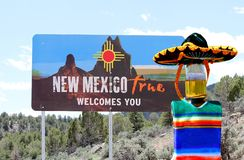 Welcome to New Mexico Cinco de Mayo beer bottle. This beer bottle is wearing a sombrero and poncho and is hanging out in New Mexico for Cinco de Mayo.  This stock image