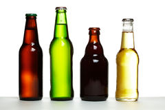 Beer bottles. Set of four beer bottles in different colours and shapes Stock Photos