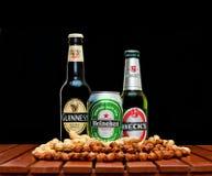 Beer bottles of Beck's , Guinness , Heineken. ZAGREB , CROATIA - JANUARY 24 ,2014 :  Beer bottles on black background, Beck's , Guinness , Heineken with peanuts Royalty Free Stock Image