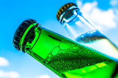 Beer in bottles with bubbles closeup on blue sky background Royalty Free Stock Photo