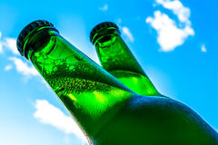 Beer in bottles with bubbles closeup on blue sky background Royalty Free Stock Image