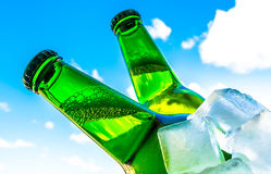 Beer in bottles with bubbles closeup in ice cubes on blue sky background Stock Photography