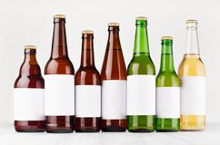 Beer bottles collection different type and colors with blank white label on white wooden board, mock up. Royalty Free Stock Images