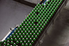 Beer bottles on the conveyor Royalty Free Stock Photos