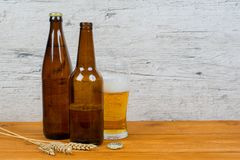 Beer bottles and glass on pub table Stock Photos