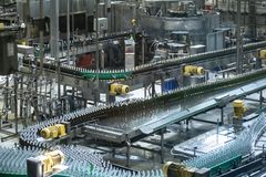 Beer bottles moving on automated conveyor line or belt. Industrial brewery and alcohol production equipment stock photography
