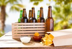 Beer bottles in wooden box and pack of potato chips,sauces.  stock photography
