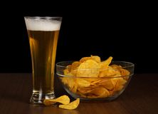 Beer and a bowl with the golden chips Stock Images