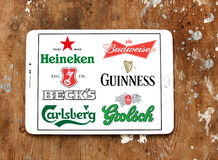 Beer brands and logos. Collection of logos and vector of most popular beer brands and producers on white tablet on rusty wooden background Royalty Free Stock Images
