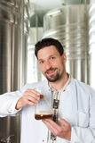 Beer brewer in his brewery examining Stock Photo