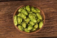 Beer brewing ingredients Hop cones in wooden bowl and wheat ears on wooden background. Beer brewery concept. Beer brewing ingredients Hop cones in wooden bowl Stock Photo