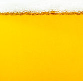 Beer bubbles. The yellow background - the detail of beer Stock Photos