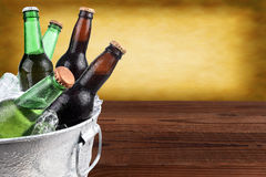 Beer Bucket with Copy Space. Closeup of a metal ice bucket filled with assorted beer bottles. Horizontal format with copy space and warm background royalty free stock photo