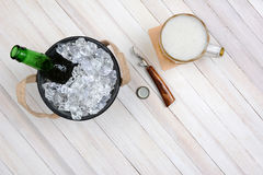 Beer Bucket Mug and Opener. Overhead shot of an ice bucket with an opened beer bottle, a mug of beer and opener on a rustic white wood table. Horizontal format royalty free stock photo