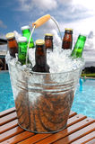 Beer Bucket on Poolside Teak Table. Close up of a beer bucket on poolside teak table. Swimming pool with beach balls and house in background. Cloudy blue sky and Stock Photos