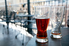Beer at Cafe. Two glasses of beer, one half full and one empty, sit on a table at an outdoor cafe Stock Images
