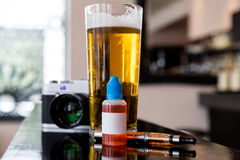 Beer, camera, vaping juice and vaporizer Royalty Free Stock Image