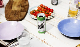 Beer can on wooden table with dishes Royalty Free Stock Photos