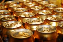 Beer cans. Gold coloured beer cans in a row royalty free stock photo