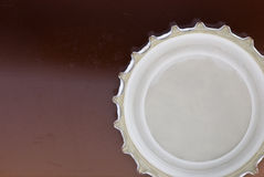 Beer cap. White beer cap on dark brown table Royalty Free Stock Photography