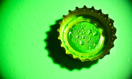 Beer cap with water drops on green Royalty Free Stock Image