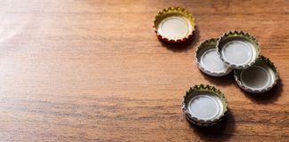 Beer caps on wooden background stock image