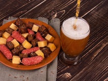 Beer, cheese and sausage. Beer with cheese and sausage plate on wooden background Royalty Free Stock Photo