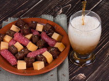 Beer, cheese and smoked sausages. Glass of beer, cheese and smoked sausages plate Stock Photo