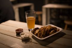 Beer, chicken wings and sauce on the table in pub. Blur background Royalty Free Stock Photography