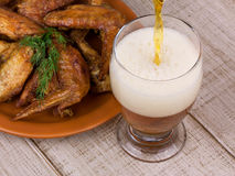 Beer and chicken wings. On wooden background Royalty Free Stock Image