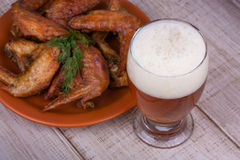 Beer and chicken wings on wooden background. Stock Images