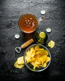 Beer with chips in a glass bowl. On black rustic background royalty free stock photography