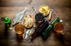 Beer with chips and squid rings in bowl and dried fish stock photography