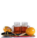 Beer for Cinco de Mayo Party. Cinco de Mayo concept with freshly poured beer, maracas, sombrero and placemat serapes on glass table isolated on white