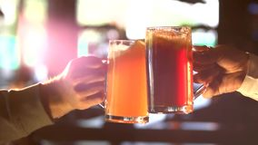Beer clinking glasses slow-mo. Clinking mugs with light beer and ale stock footage