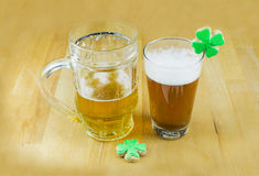 Beer and clover cookies stand on a wooden bar counter Royalty Free Stock Photo