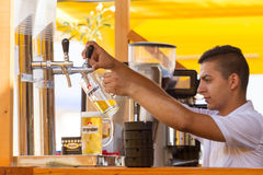 Beer. A cold beer in a pint cup at Tuborg Green Fest, ready to be served. A waiter fill a pint of beer stock photos