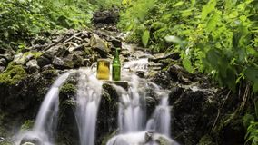 Beer cooled in waterfall spring stock footage
