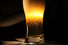 Beer On Dark. High glass of fresh beer with blebs and lot of foam on dark background Royalty Free Stock Images