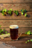Beer dark lager, brown ale on wooden table in bar or pub Stock Photography