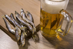 Beer and dried fish on wooden table. Stock Photography