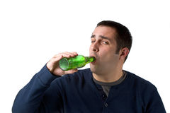 Beer Drinker. A young man drinking a bottle of beer isolated over a white background Royalty Free Stock Photos