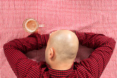 Beer drinker. Bald beer drinker sitting in the bar with a glass of cold lager on the table Stock Photography