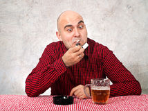 Beer drinker lighting up a cigarette Royalty Free Stock Image