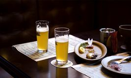 Beer and eaten meals. Two glasses of partially drunk beer or lager with used plates on wooden table, black background Stock Photography