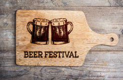 Beer festival sign with two beer mugs, cutting board. Beer festival sign with two hand drawn beer mugs on cutting board. Wooden background. Studio shot Royalty Free Stock Image