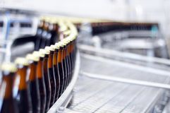 Beer filling in a brewery - conveyor belt with glass bottles. Close up Stock Photos