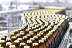 Beer filling in a brewery - conveyor belt with glass bottles. Beer filling machine in a brewery - conveyor belt with glass bottles Stock Photo